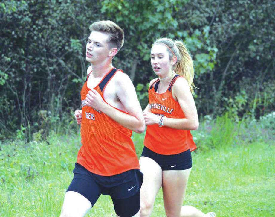 Edwardsville junior Andrew Delmore, left, and Edwardsville senior Jaycee Hudson compete in the combined junior-senior boys' and girls' race in Monday's Tiger Finale at SIUE. Hudson won the girls' race. Photo: Scott Marion/Intelligencer