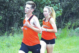 Edwardsville junior Andrew Delmore, left, and Edwardsville senior Jaycee Hudson compete in the combined junior-senior boys' and girls' race in Monday's Tiger Finale at SIUE. Hudson won the girls' race.