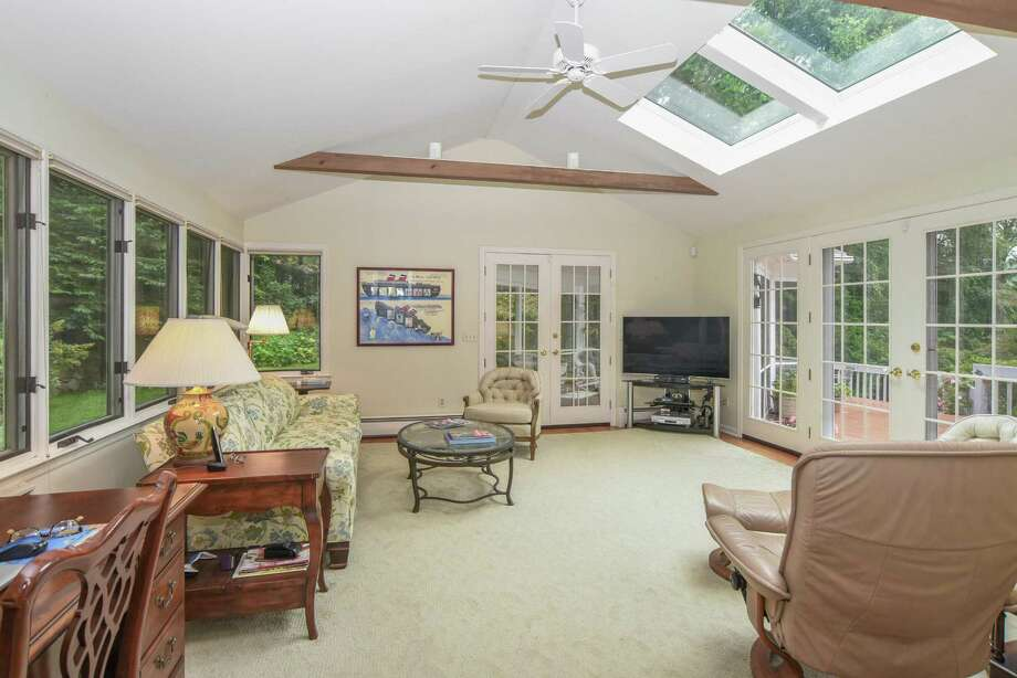 The family room at 70 Linden Tree Road in Wilton is adjacent to a screened-in porch and expansive deck. Photo: James Patrick Cooper / James Patrick Cooper