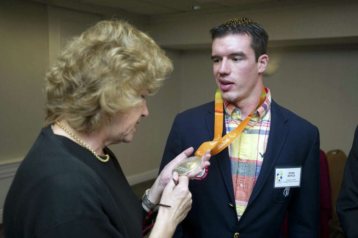 Barbara Rittner, the mother of the late Chelsea Cohen, looks at the 2016 silver medal of Ryan Boyle, the recipient of the 2018 Chelsea Cohen Courage Award, during the Fairfield County Sports Commision's Sports Night at the Stamford Marriott in downtown Stamford, Conn. on Monday, Oct. 15, 2018.