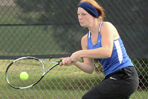 Marquette Catholic senior Maria Wendle returns a shot during her three-set semifinal victory Monday at the Triad Class 1A Sectional. Wendle finished second to earn her first trip to state.