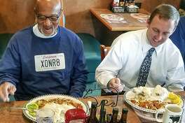 In this photo provided by California Innocence Project Horace Roberts, left, has his first meal after walking out of Avenal State Prison with California Innocence Project managing attorney Michael Semanchik in Avenal, Calif., Oct. 3, 2018. Roberts, wrongly convicted of murdering his lover two decades ago has been exonerated and new arrests have been made in the case. (California Innocence Project via AP)