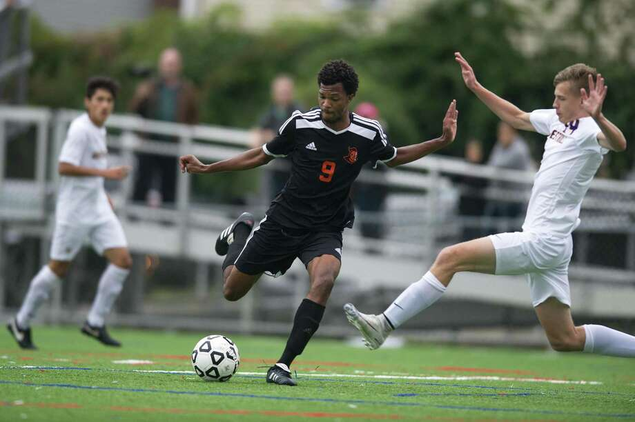 Stamford High junior forward Kenly Lalanne pulls back to fire a shot on goal ahead of sliding Westhill High senior Eric Zagaja during the Vikings' 3-1 victory on the upper field at Stamford High on Friday. Photo: Michael Cummo / Hearst Connecticut Media / Stamford Advocate