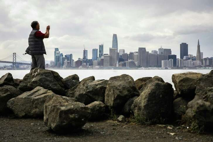 Liem Phan of Oakland takes a photo of the skyline from Treasure Island in San Francisco on Wednesday, October 3, 2018.