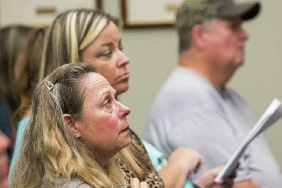 Crosby Independent School District board of trustees attendees listen to the names of staff members who's contracts will be terminated by the end of the meeting, Monday, Oct. 15, 2018, in Crosby.