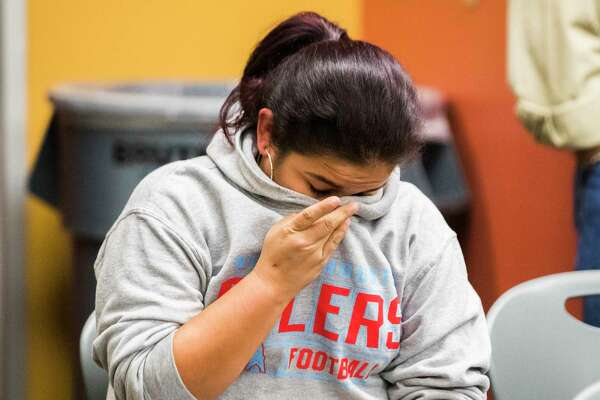 A Crosby resident not wanting to be identified, dries her tears as the Crosby Independent School District board of trustees terminate the contract termination of some staff members, Monday, Oct. 15, 2018, in Crosby.