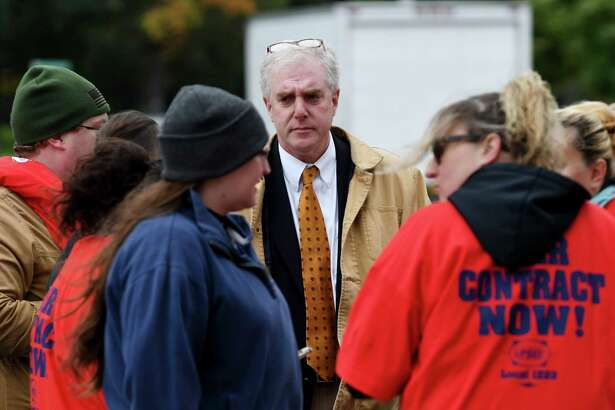 Albany Treasurer Darius Shahinfar, center, speaks with Mohawk Ambulance Service workers during a demonstration rally near the Mohawk offices on Central Avenue on Monday, Oct. 15, 2018, in Albany, N.Y. The emergency medical staffers are asking for better pay and working conditions from the local ambulance company since their contract expired in April. They are represented by the United Professional Services Employees Union. (Will Waldron/Times Union)