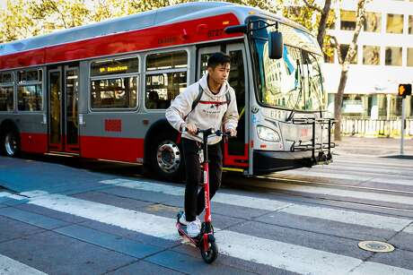 Andrew Lee rides on a Scoot scooter on Market and 5th Streets in San Francisco, California, on Monday, Oct. 15, 2018.