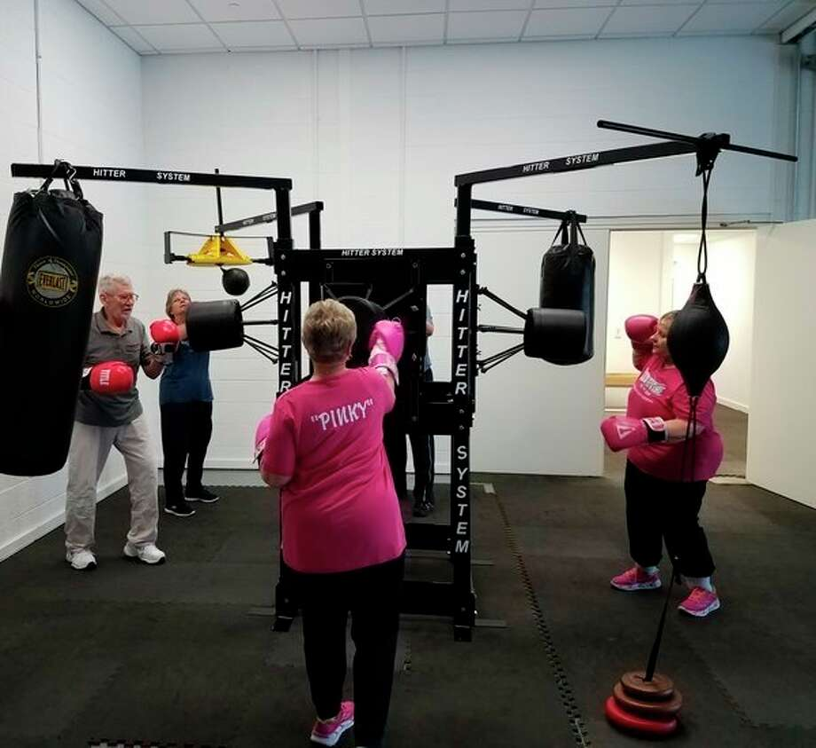 Elaine 'Pinky' Embry, 74, Marge 'Blinky' Williams, 74, Eugene 'UCII' Moore, 84, and Sharon 'Belle' Winchester, 71, train on The Hitter System designed by Brad Kohler atRock Steady Boxing Mid-Michigan.(Photo provided/Stacey Hitsman)