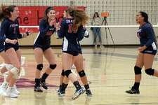 GFA volleyball players, from left, Kirway Carey, Kristiana Modzelewski, Elena Mota and Leah Attai celebrate a point during the Dragons' 3-0 win over King on Saturday during homecoming.
