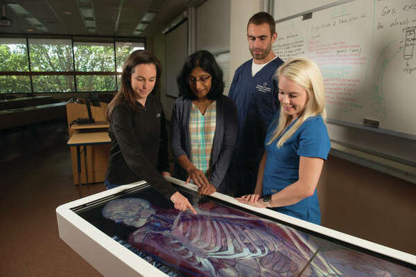 SIUE School of Nursing students use the Anatomage Table under the direction of Dr. Chaya Gopalan (middle) to explore various anatomical structures and their interplay.