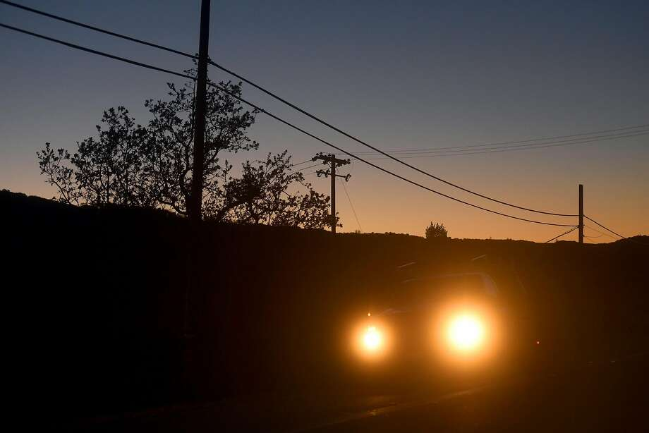 A car passes power lines Highway 12 near Glen Ellen, Calif., on Monday, Oct. 15, 2018. Some customers in the region remain without power after PG&E cut electric service in hopes of preventing fires amid red flag fire warnings. Photo: Noah Berger / The Chronicle