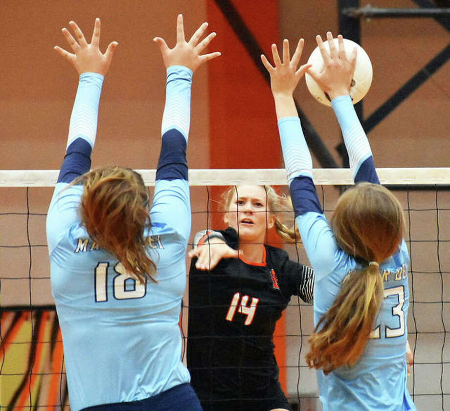 Edwardsville's Maddie Isringhausen tries to power an attack through a double block up up by Breese Mater Dei's 6-foot Carlee Wise (left) and 5-11 Jessie Timmermann (right) during the Tigers' three-set victory Monday night in Edwardsville. Isringhausen is the daughter of former St. Louis Cardinals pitcher Jason Isringhausen. Photo: Matthew Kamp / Hearst Illinois