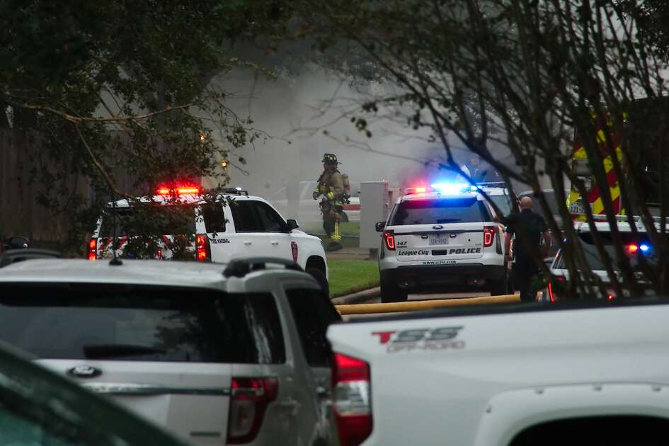 Emergency vehicles block the road as League City police and fire crews respond to a house fire off Eastland St. in League City Tuesday, Oct 16.
