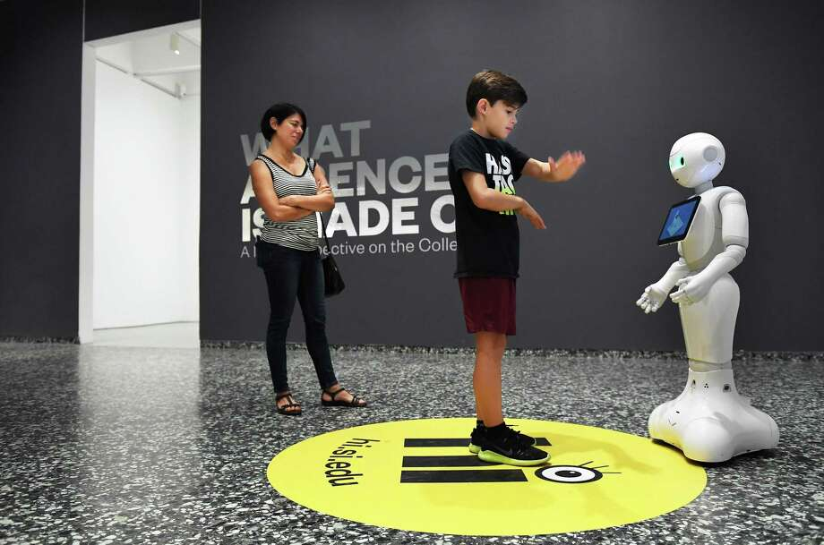Emilia Labrada watches her son, Julian Allan, 12, interact with Pepper, a humanlike robot at the Smithsonian's Hirshhorn Museum. Photo: Washington Post Photo By Matt McClain / The Washington Post