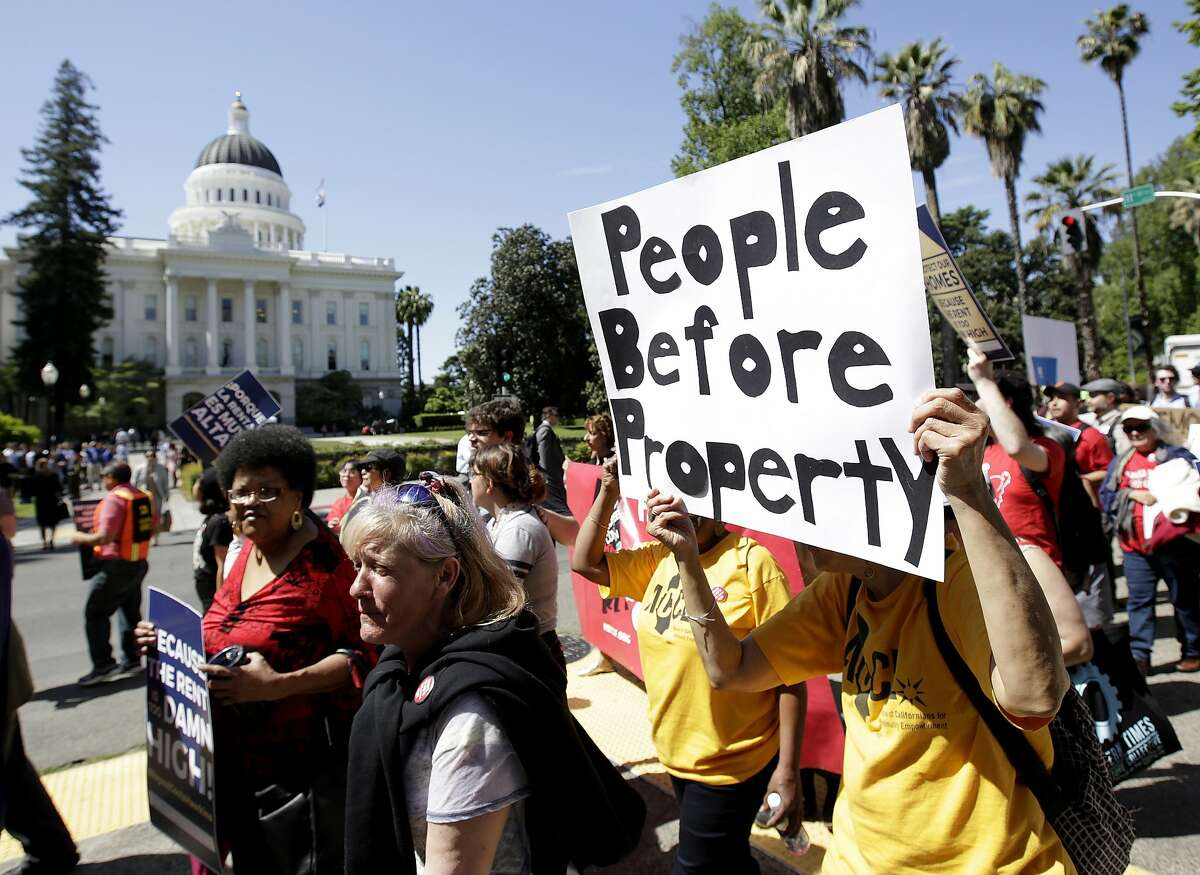 ADVANCE FOR RELEASE SATURDAY, OCT. 6, 2018, AND THEREAFTER - FILE - In this April 23, 2018, file photo rent control supporters march past the Capitol in Sacramento, Calif. Californians who rent apartments built after 1995, single-family homes or condominiums have limited protections from rising costs under a state law passed that year that restricts rent control. That could change if voters pass Proposition 10 in November. It would overturn the 1995 law and open the door to more rent control in cities and counties across the state. (AP Photo/Rich Pedroncelli, File)