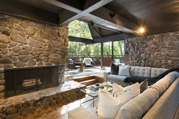 The living room's stone fireplace at 252 The Uplands in Berkeley offers a sitting ledge and stands beside a sitting area that opens to a deck.