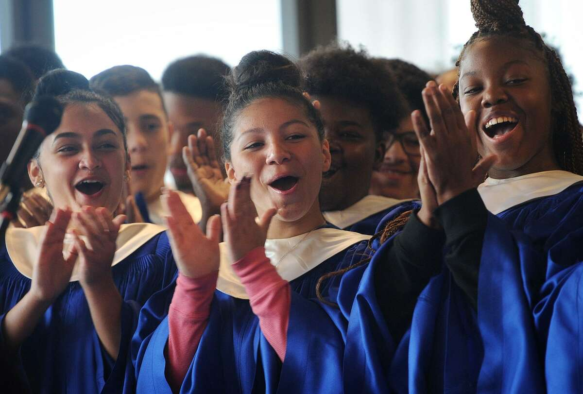 From left, Harding High School chorus members Alize Rivas, 16; Frances Maisonet; 16, and Janae Hunter, 15; applaud music teacher Sheena Graham during her Connecticut Teacher of the Year ceremony at Harding High School in Bridgeport on Tuesday.