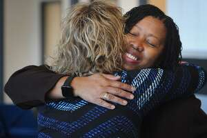 2019 Teacher of the Year Harding High School music teacher Sheena Graham, facing, is hugged by 2011 Teacher of the Year Kristen Record, a physics teacher at Bunnell High School in Stratford, before the ceremony at Harding High School in Bridgeport, Conn. on Tuesday, October 16, 2018.