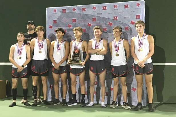 The Hargrave High School boys cross country team celebrates with its trophy and medals after winning the District 21-4A meet on October 11 in Huffam