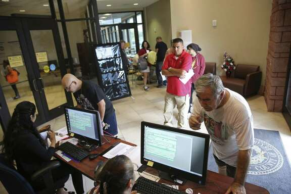 Juan Peña, 79, lower right, inquires about his voter registration status at the Bexar County Elections Department, Tuesday, Oct. 9, 2018. Tuesday was the deadline to register in order to vote in the upcoming November 6 general election. Officials said the department had a steady flow of people registering or changing their address in the days leading up to the deadline but on Tuesday there was a marked increase.