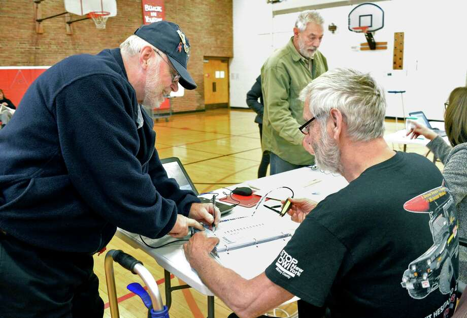 Ralph LeBarron, left, signs in to vote on the Guilderland Central School District Capital improvement project with election inspector Tom Person at Westmere Elementary Schoolwith Tuesday Oct. 16, 2018 in Guilderland, NY.  (John Carl D'Annibale/Times Union) Photo: John Carl D'Annibale, Albany Times Union / 20045145A