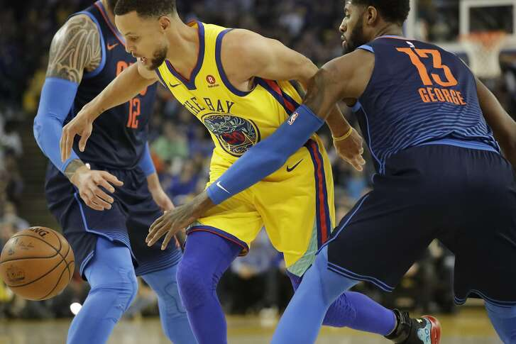 Golden State Warriors guard Stephen Curry (30) splits Oklahoma City Thunder center Steven Adams (12) and forward Paul George (13) to drive on the basket on Saturday, Feb. 24, 2018 in Oakland, CA.