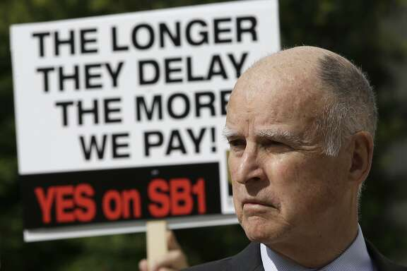 FILE - In this April 5, 2017, file photo, California Gov. Jerry Brown waits to speak a rally in Sacramento, Calif., to promote SB1, a bill to raise gas and car taxes to generate $5 billion per year for road repairs. As the political battle to overturn the tax increase intensified, the state transportation agency coordinated frequently with the public relations firm working to block the repeal on behalf of unions, construction companies and local governments, emails obtained by The Associated Press show. (AP Photo/Rich Pedroncelli, File)