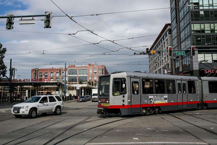 The Muni T line arrives at the 4th and King intersection on Wednesday, October 3, 2018 in San Francisco, Calif. while a car takes a left-hand turn in front of the rail. The T line is known for the major issues that riders face including overcrowding, delays and the risk of car collisions because of left-hand turns. Photo: Brian Feulner / Special To The Chronicle