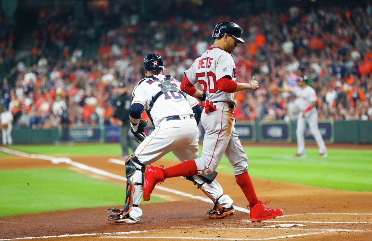 Boston Red Sox Mookie Betts (50) crosses home plate on a Boston Red Sox J.D. Martinez (28) double during the first inning of Game 3 of the American League Championship Series at Minute Maid Park on Tuesday, Oct. 16, 2018, in Houston.