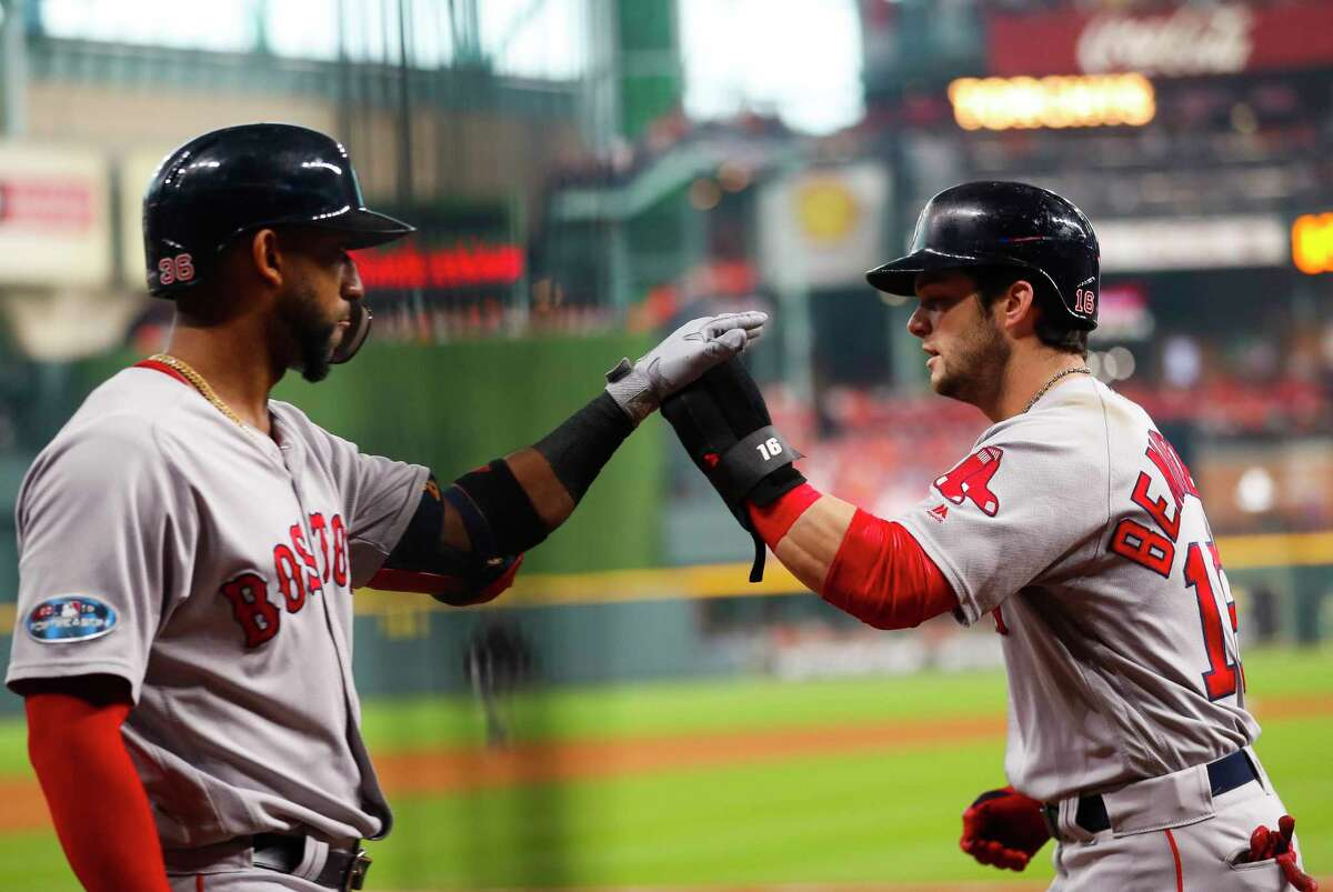Boston Red Sox Andrew Benintendi (16) is welcomed back to the dugout on a ground out by Boston Red Sox Xander Bogaerts (2) during the first inning of Game 3 of the American League Championship Series at Minute Maid Park on Tuesday, Oct. 16, 2018, in Houston.