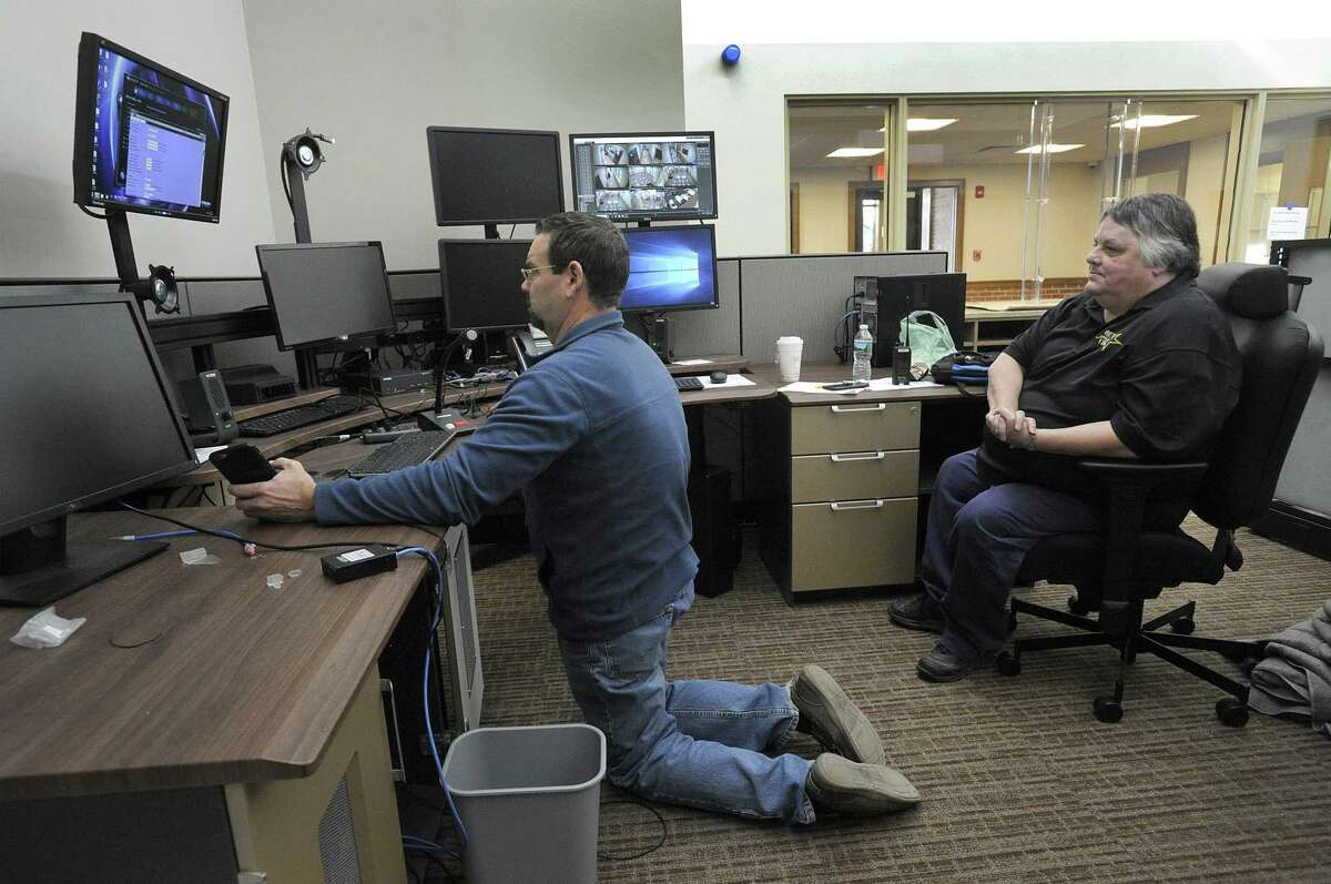 Brooks Gianakos, left, with the utilities commission, and Mary Ann Broderick, a dispatcher, work to ready the dispatch center at the new Bethel Police Department for use by Tuesday evening, Oct. 16, 2018.