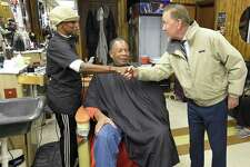 """Mack Homer of Stamford sits in the barbers chair as Democratic Governor candidate Ned Lamont greets Thomasina Bradford, a barber/stylist at Superior Barber and Beauty shop in Stamford, Connecticut., Tuesday, Oct. 16, 2018. Lamont was on a short city tour to share recently announced policy proposals on """"entrepreneurship and workforce development"""" by expanding access to higher education and training."""