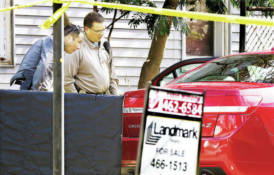 "An Alton police evidence officer, left, looks into the car still containing the body of Eldon ""Twirp"" Williams, 87, with Madison County Coroner's Office Chief Investigator Kelly Rogers, right, Tuesday in the driveway of a house for sale in the 200 block of West Delmar Avenue in Alton. Williams was apparently found shot inside the car. Some 20 police officers from Alton and the Madison County Sheriff's Department converged on the scene and canvassed the neighborhood for clues. Police said that ""a person of interest"" was taken into custody. Williams, a real estate broker, was a Godfrey village trustee. Additional photos at thetelegraph.com. Photo: John Badman 