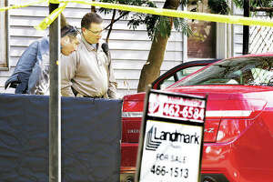 "An Alton police evidence officer, left, looks into the car still containing the body of Eldon ""Twirp"" Williams, 87, with Madison County Coroner's Office Chief Investigator Kelly Rogers, right, Tuesday in the driveway of a house for sale in the 200 block of West Delmar Avenue in Alton. Williams was apparently found shot inside the car. Some 20 police officers from Alton and the Madison County Sheriff's Department converged on the scene and canvassed the neighborhood for clues. Police said that ""a person of interest"" was taken into custody. Williams, a real estate broker, was a Godfrey village trustee. Additional photos at thetelegraph.com."