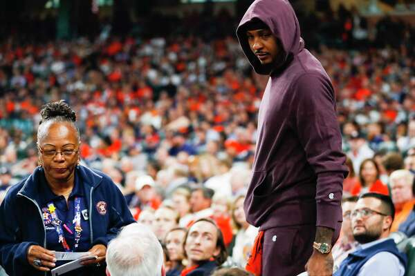 Houston Rockets player Carmelo Anthony finds his seat during Game 3 of the American League Championship Series at Minute Maid Park on Tuesday, Oct. 16, 2018, in Houston.