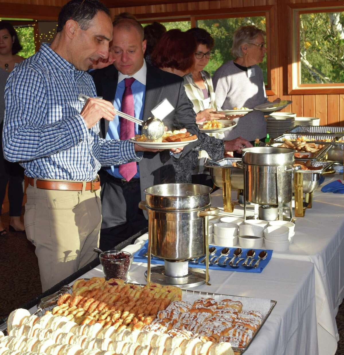 Guests Mike Nahom, foreground, and Dean Aita make their way through the buffet line during the event.