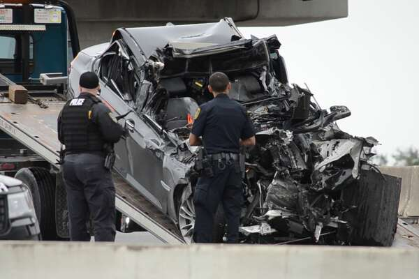 Houston police officers investigate a fatal crash along the Southwest Freeway near Westpark Drive on Tuesday, Oct. 16, 2018.