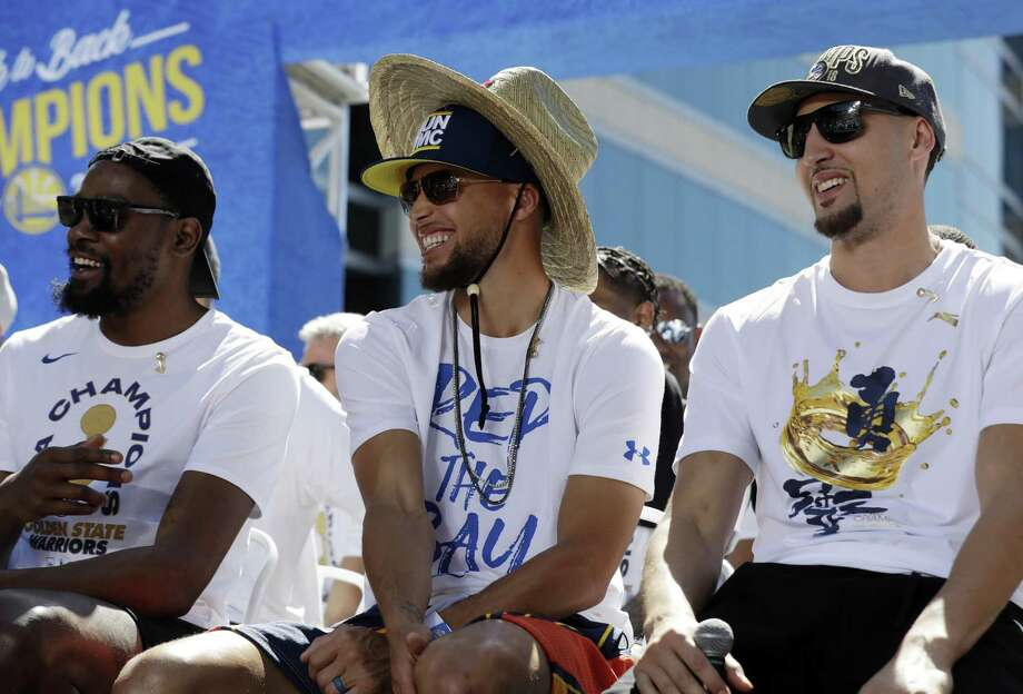 Golden State Warriors' Kevin Durant, left, Stephen Curry, center, and Klay Thompson smiles during a parade after winning the NBA basketball championship Tuesday, June 12, 2018, in Oakland, Calif. Photo: Marcio Jose Sanchez / AP / Copyright 2018 The Associated Press. All rights reserved.