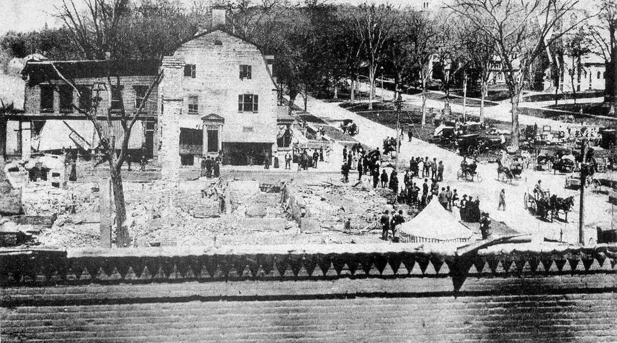 The Great Fire of May 1902 swept through the business district of New Milford, destroying much of the Railroad to Main streets and Bridge to Bank streets block in smoke and ashes. This view looking north shows many of the townsfolk milling around the ruins, even as a shantytown grew on the south end of the Village Green to provide temporary homes to the displaced merchants. The large building at the north corner of Bank and Main is the United States Hotel,which survived the blaze only to be razed during the 1920s to make room for a pharmacy. On the nearer street corner are the remains of the New England House Hotel, the other half of the village center's proud bookends hotels of the era. If you have a