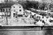 "The Great Fire of May 1902 swept through the business district of New Milford, destroying much of the Railroad to Main streets and Bridge to Bank streets block in smoke and ashes. This view looking north shows many of the townsfolk milling around the ruins, even as a shantytown grew on the south end of the Village Green to provide temporary homes to the displaced merchants. The large building at the north corner of Bank and Main is the United States Hotel,which survived the blaze only to be razed during the 1920s to make room for a pharmacy. On the nearer street corner are the remains of the New England House Hotel, the other half of the village center's proud bookends hotels of the era. If you have a ""Way Back When"" photograph to share, contact Deborah Rose at drose@newstimes.com or 860-355-7324."