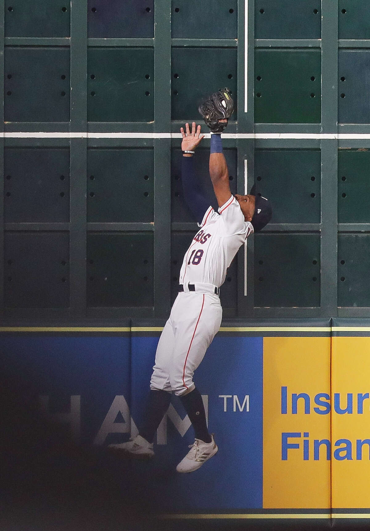 Houston Astros Tony Kemp (18) catches a fly ball from Boston Red Sox Steve Pearce (25) against the wall to end the top of the third inning of Game 3 of the American League Championship Series at Minute Maid Park on Tuesday, Oct. 16, 2018, in Houston.