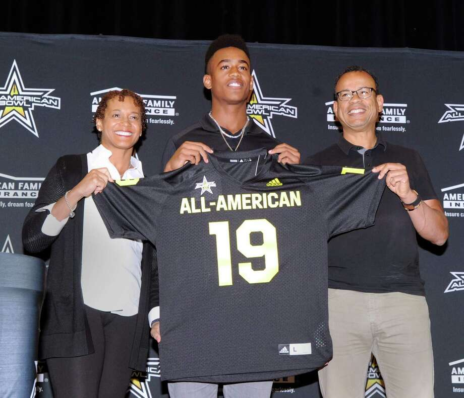 With his smiling parents, Dr.Cassandra Tribble, left, and Claude Johnson by his side, Brunswick School football player, Cornelius Johnson, center, a wide receiver, holds his All-American football jersey from the organizers of the national All-American Bowl by American Family Insurance during a presentation ceremony at Brunswick School where Johnson plays and is a senior, Greenwich, Conn., Tuesday, Oct. 16, 2018. The bowl game Johnson will play in will be played in San Antonio, Texas, on January 5, 2019. Photo: Bob Luckey Jr. / Hearst Connecticut Media / Greenwich Time