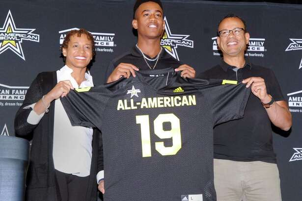 With his smiling parents, Dr.Cassandra Tribble, left, and Claude Johnson by his side, Brunswick School football player, Cornelius Johnson, center, a wide receiver, holds his All-American football jersey from the organizers of the national All-American Bowl by American Family Insurance during a presentation ceremony at Brunswick School where Johnson plays and is a senior, Greenwich, Conn., Tuesday, Oct. 16, 2018. The bowl game Johnson will play in will be played in San Antonio, Texas, on January 5, 2019.