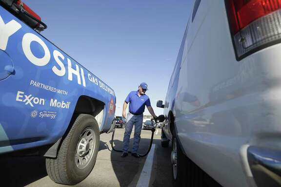 Bobby Perry with Yoshi gas delivery fills up a commuter van Friday, Oct. 12, 2018, in Houston.