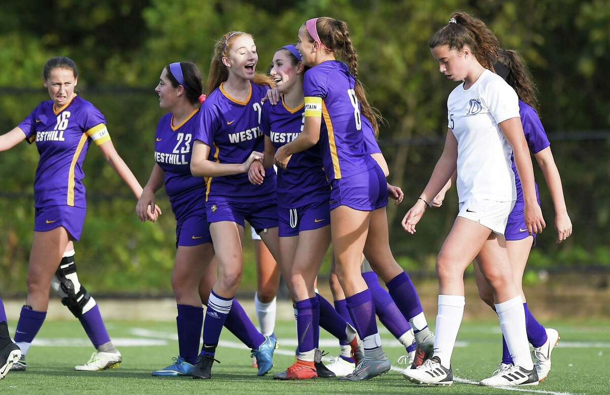 Westhill's Corinne Dente (9), center, celebrates her goal against Darien in the first half of an FCIAC girls soccer game in Stamford, Connecticut., Tuesday, Oct. 16, 2018.