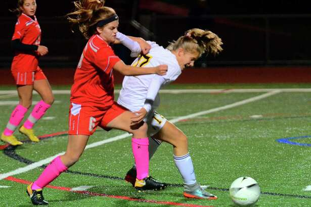 Weston's Amelia Rudolph tries to hold back Masuk's Kacey Lawrence during Tuesday's game.