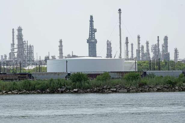 "Storage tanks at a refinery along the waterway are shown Thursday, July 26, 2018, in Port Arthur, Texas. The oil industry wants the government to help protect some of its facilities on the Texas Gulf Coast against the effects of global warming. One proposal involves building a nearly 60-mile ?""spine?"" of flood barriers to shield refineries and chemical plants. Many Republicans argue that such projects should be a national priority. But others question whether taxpayers should have to protect refineries in a state where top politicians still dispute whether climate change is real. (AP Photo/David J. Phillip)"
