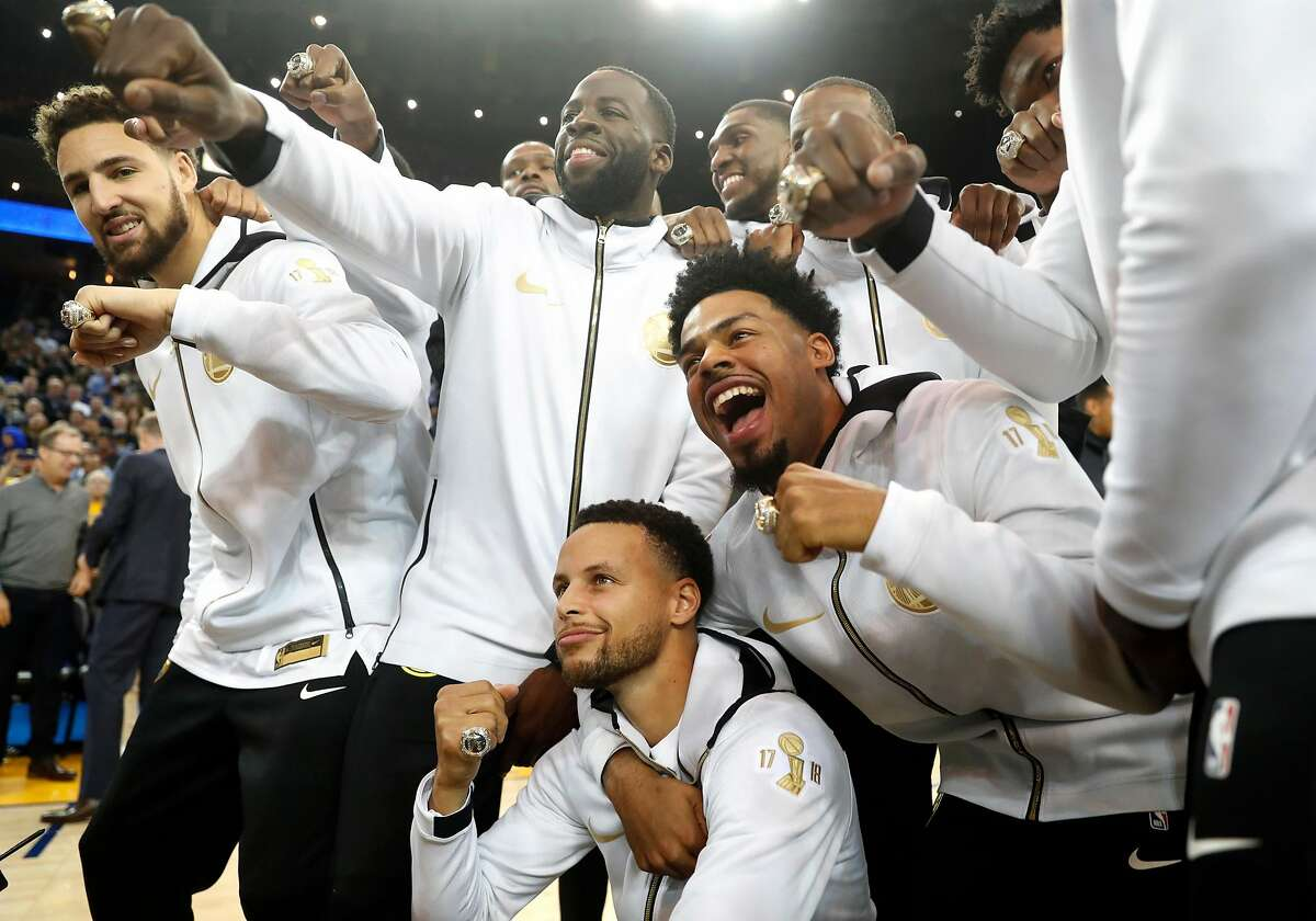 Golden State Warriors' Stephen Curry, Quinn Cook, Draymond Green and Klay Thompson join teammates in showing off their 2017-18 NBA Championship rings after ceremony before Opening Night game against Oklahoma City Thunder at Oracle Arena in Oakland, Calif. on Tuesday, October 16, 2018.