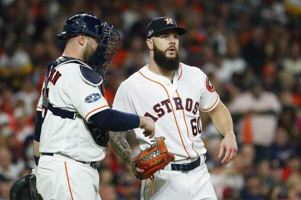 Houston Astros starting pitcher Dallas Keuchel (60) and catcher Brian McCann (16) meet at the mound after walking Xander Bogaerts (2) during the third inning of Game 3 of the American League Championship Series at Minute Maid Park on Tuesday, Oct. 16, 2018, in Houston.